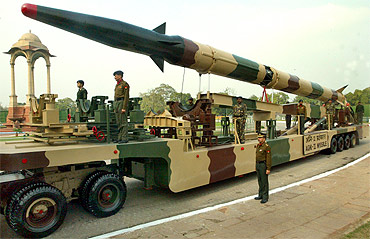 Soldiers stand beside the Agni missile during a media briefing