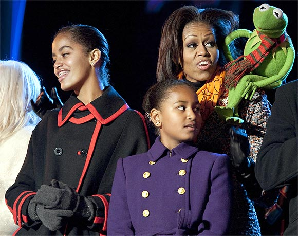 U.S. first lady Michelle Obama sings a Christmas carol with her daughters Malia (L) and Sasha and Kermit the Frog during the lighting of the National Christmas Tree in Washington