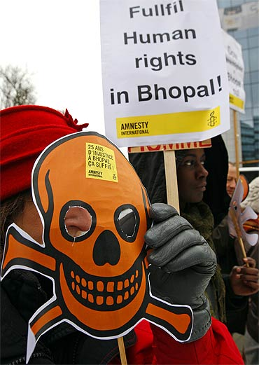 Activists of Amnesty International wear masks representing victims of the Bhopal gas tragedy during a demonstration outside the European headquarters of Dow Chemicals in Brussels