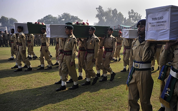 The word shaheed is written on the caskets of soldiers killed in a cross-border attack along the Pakistan-Afghan border, as their bodies are being carried for funeral prayers in Peshawar