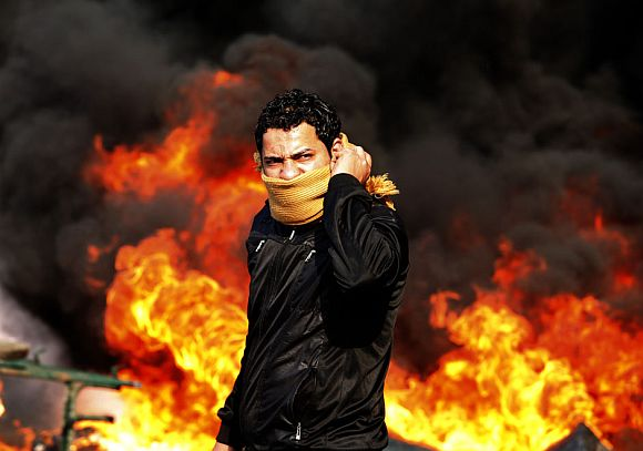 A protester stands in front of a burning barricade during a demonstration in Cairo January 28, 2011