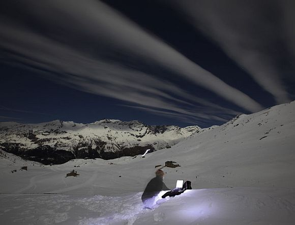Switzerland's photographer Denis Balibouse files his pictures under a full moon sky from Mont-Cenis Pass Road in Lanslebourg during the Grande Odyssee sled dogs race January 19, 2011. This picture was taken with a long exposure