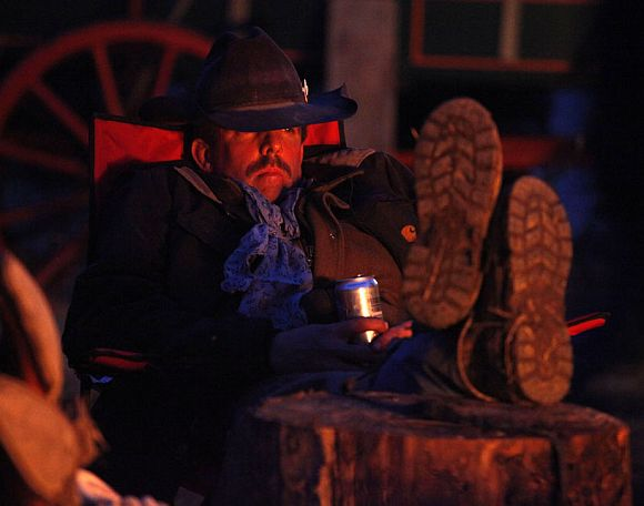 Wrangler Dale Wetz rests by the campfire after the group had gathered approximately 350 horses during Montana Horses' spring drive outside Three Forks, Montana April 22, 2011