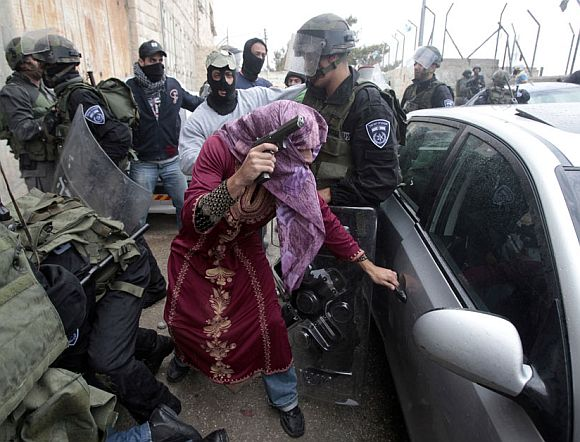 An undercover Israeli policeman dressed as a Palestinian woman opens a car door after detaining a Palestinian protester during clashes in Shuafat refugee camp, in the West Bank near Jerusalem May 15, 2011