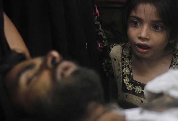 Eight-year-old Sumayya, whose uncle, Imran Ali, was injured in a shootout by unidentified gunmen, looks at him as he is brought to a hospital for treatment in Karachi August 23, 2011