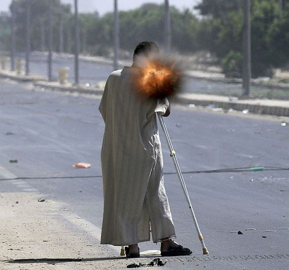 A rebel on crutches fires a rocket propelled grenade while fighting on the front line in Sirte September 24, 2011
