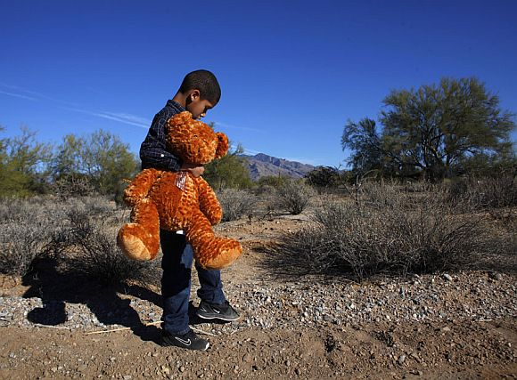 Nine-year-old Dante Mitchell, classmate of nine-year-old Christina Green, holds a stuffed bear he brought to her funeral in Tucson, Arizona January 13, 2011. Green was killed in the January 8 shooting that left six dead and wounded US Representative Gabrielle Giffords