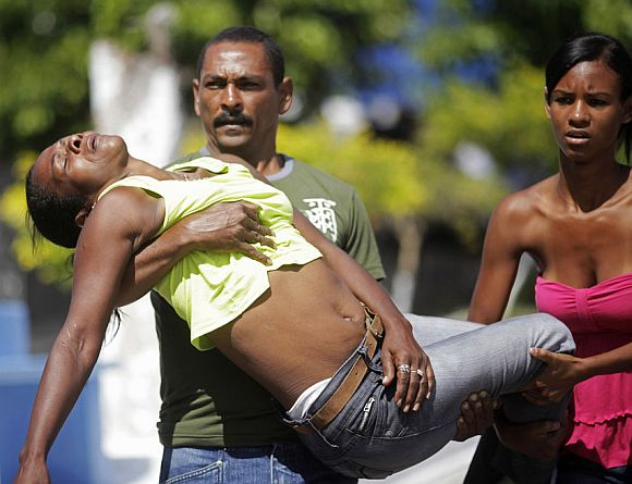 Relatives of one of the victims of a shooting at Tasso da Silveira school carry a family member who had fainted while attending the funeral at Realengo cemetery in Rio de Janeiro April 8, 2011