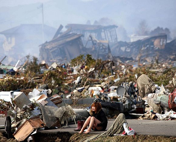 A woman cries while sitting on a road amid the destroyed city of Natori, Miyagi Prefecture in northern Japan March 13, 2011, after a massive earthquake and tsunami