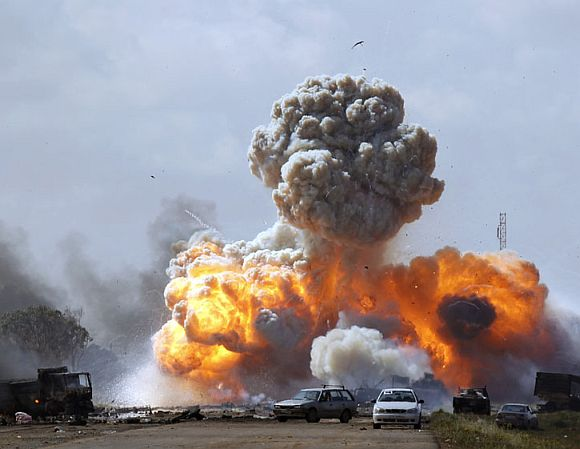 Vehicles belonging to forces loyal to Libyan leader Muammar Gaddafi explode after an air strike by coalition forces, along a road between Benghazi and Ajdabiyah March 20, 2011