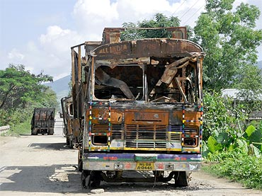 Burnt trucks on National Highway 39, which connects Manipur to mainland India via Nagaland and Assam