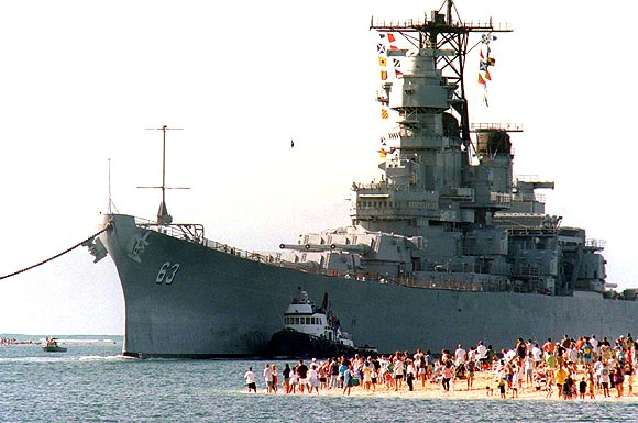 The battleship USS Missouri, Mighty Mo, looms over a gathering of fans as it returns to Pearl Harbor. The USS Missouri, the ship where the Japanese and the United States signed the agreement to end World War II, will be used as a museum near the memorial to the USS Arizona