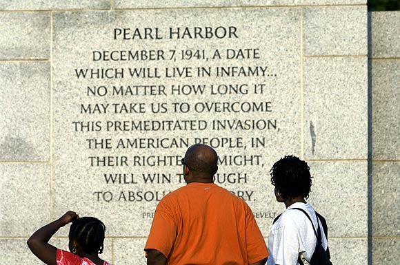 A family reads an inscription by President Franklin Delano Roosevelt on the bombing of Pearl Harbour