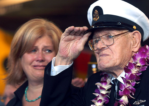 Lois Deininger of San Francisco watches her father, Pearl Harbor survivor, Edward Gaulrapp of Freeport Illinois, salute during the commemoration marking the 66th anniversary of Pearl Harbour attack