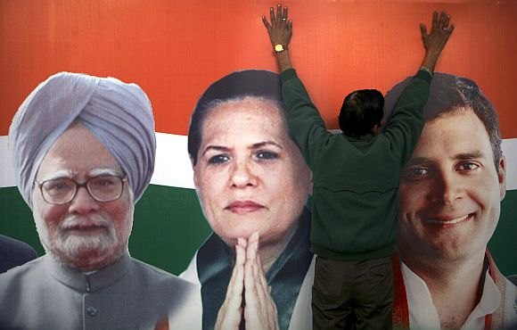 A worker installs a hoarding of the Congress party