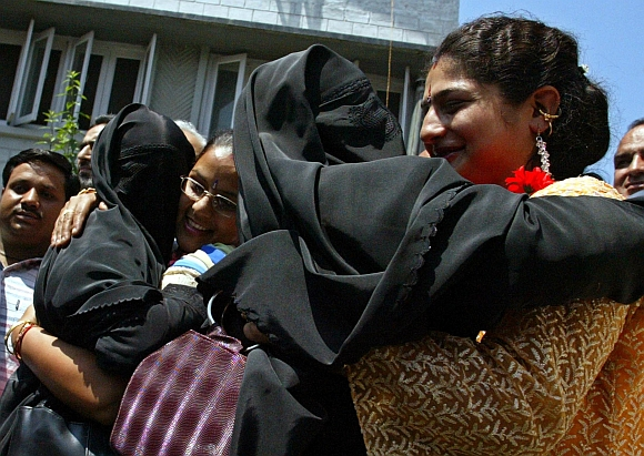 Migrant Kashmiri Hindu women hug veiled Kashmiri Muslim activists from the All Parties Hurriyat Conference before their meeting in Srinagar