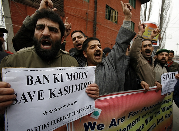 Kashmiri activists belonging to the moderate faction of All Parties Hurriyat Freedom Conference shout pro-freedom slogans while holding a placard and banner during a demonstration in Srinagar