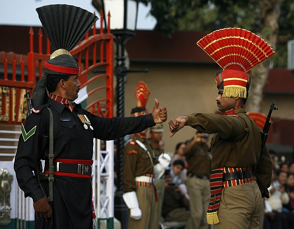 Pakistani Ranger and Indian Border Security Force soldiers gesture during a daily parade at the Pakistan-India joint check post at Wagh border, on the outskirts of Lahore