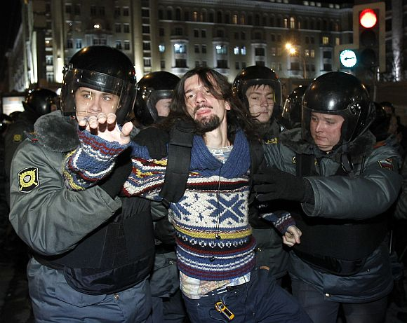 Policemen detain an activist during rally to protest against the results of the parliamentary elections and the policies conducted by Russian authorities in Moscow