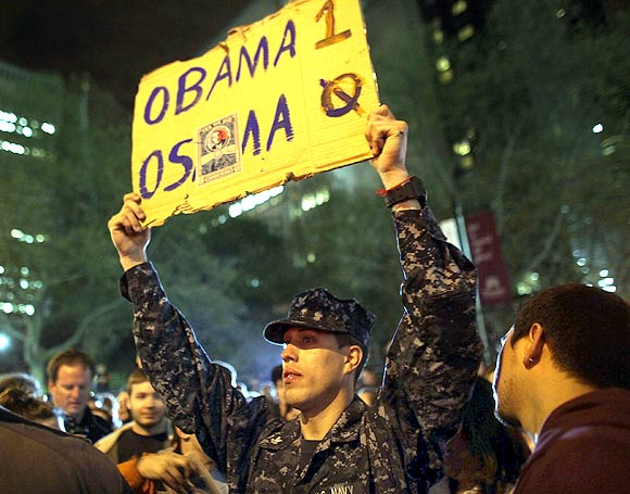 A man holds up a scoreboard displaying Obama - one, Osama - nil,  as thousands of people celebrate in the streets at Ground Zero, the site of the World Trade Centre, waving American flags and honking horns to celebrate the death of Al Qaeda founder and leader Osama bin Laden on May 1