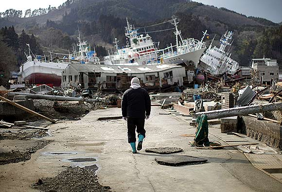 A man walks next to port area destroyed by the earthquake and tsunami in Kessenuma town, in Miyagi prefecture March 28