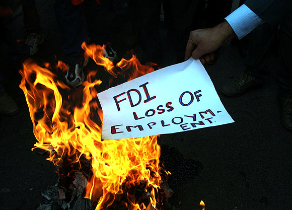 An activist of Shiv Sena burns a pamphlet during a protest against FDI in retail sector, in Jammu on November 30