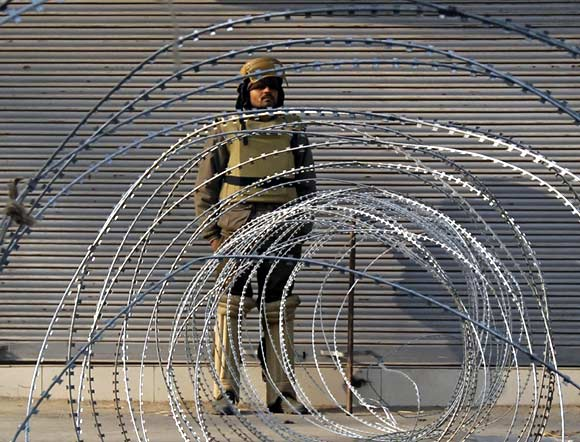 A policeman stands guard behind a barricade in Srinagar