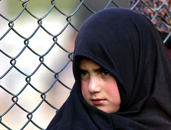 A girl watches a procession in Srinagar