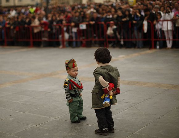 A child dressed up as a Spanish legionnaire looks at another holding a toy during the Holy Week in Malaga, southern Spain