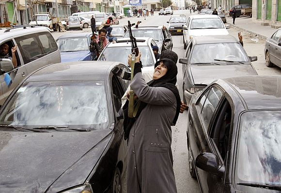 A woman rebel fighter supporter shoots an AK-47 rifle as she reacts to the news of the withdrawal of Libyan leader Muammar Gaddafi's forces from Benghazi March 19