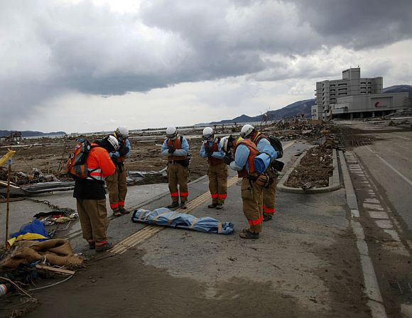 Rescue workers pay their final respects to a dead body retrieved from the rubble in Rikuzentakat, Iwate Prefecture, days after the area was devastated by an earthquake and tsunami March 17, 2011
