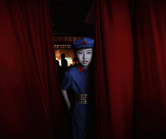 A schoolgirl participant, dressed as a Chinese Red Army soldier, walks through a red curtain during a revolutionary song singing competition to celebrate the upcoming 90th anniversary of the founding of the Communist Party of China (CPC), in Chongqing municipality June 30, 2011