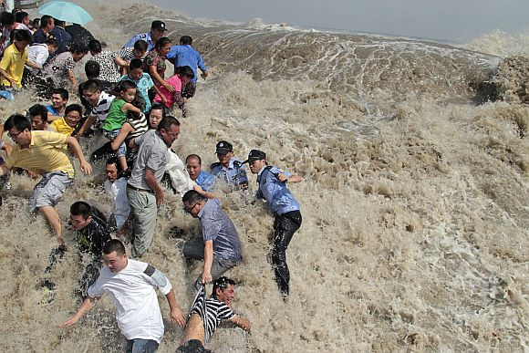 Policemen and residents run as waves from a tidal bore surge past a barrier on the banks of Qiantang River in Haining, Zhejiang province August 31, 2011. As Typhoon Nanmadol approaches eastern China, the tides and waves in Qiantang River recorded its highest level in 10 years