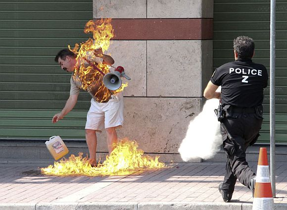 A man sets himself on fire outside a bank branch in Thessaloniki in northern Greece September 16, 2011. The 55-year old man had entered the bank and asked for a renegotiation of his overdue loan payments on his home and business, according to police, which he could not pay, but was refused by the bank