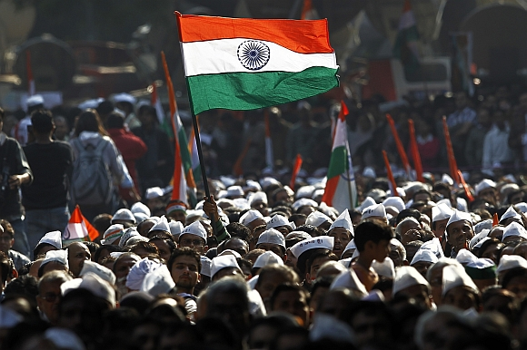A supporter of Hazare holds the India flag during Hazare's day-long hunger strike in New Delhi