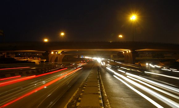 Traffic moves under a flyover along a busy road in New Delhi