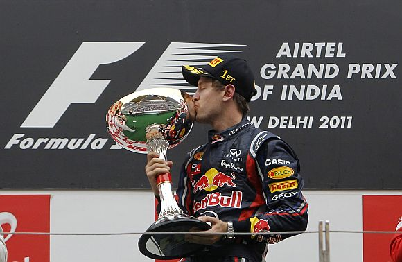 Red Bull Formula One driver Vettel kisses his trophy after winning the first Indian F1 Grand Prix at the Buddh International Circuit in Greater Noida