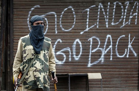 An security personnel stands guard near a closed shop during a curfew in Srinagar
