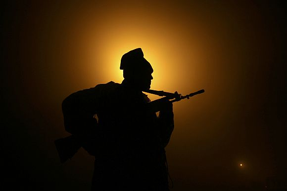 A BSF soldier patrols near fencing at India-Pakistan border at Suchetgarh near Jammu