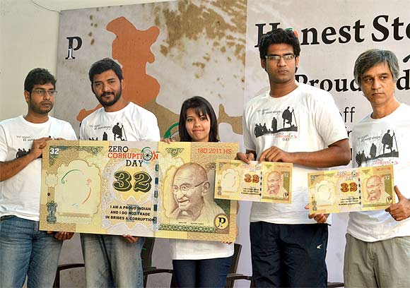 Members of 'Proud Indians' display a Rs 32 note symbolising the limit of their per day expenditure during the walkathon
