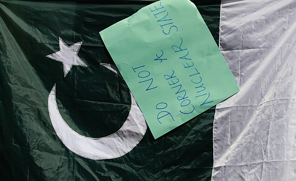 A placard hangs on a Pakistan flag during a protest against the US