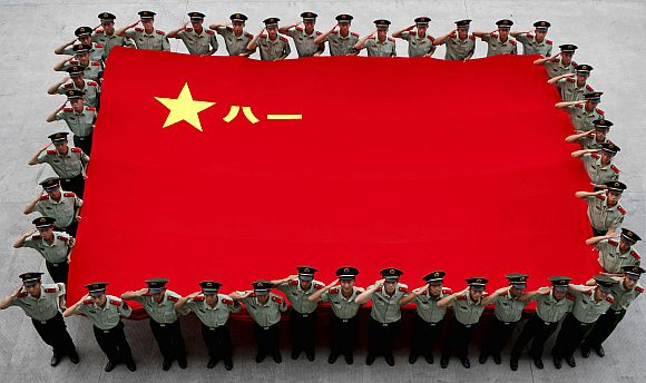 Paramilitary policemen salute as they hold a Chinese PLA flag to celebrate the anniversary of the founding of the PLA in Hangzhou, China