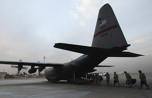 Members of the US military board an Air Force C-130 transport plane to leave Iraq at the Baghdad Diplomatic Support Center in Baghdad
