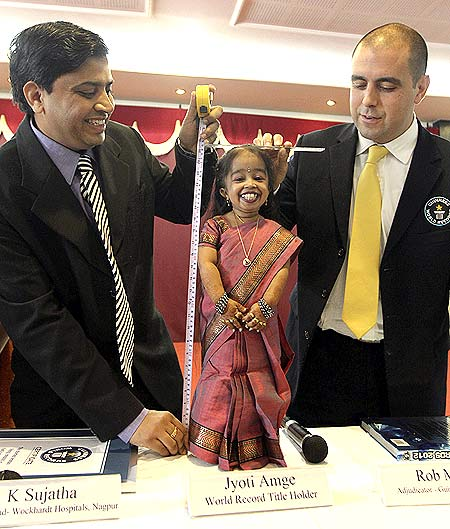 The Guinness World Records adjudicator Rob Molloy (R) and Indian doctor K. Sujatha (L) measure the height of Jyoti Amge, the world's shortest living woman
