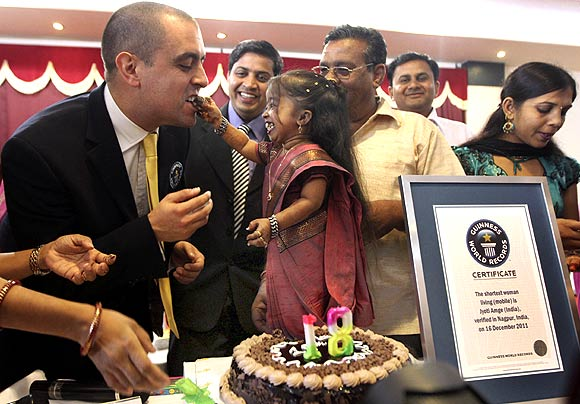 Jyoti Amge (C), the world's shortest living woman, offers a piece of cake to the Guinness World Records adjudicator Rob Molloy on her 18th birthday in Nagpur