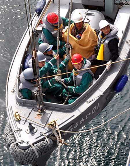 Shinkawa, who was swept out to sea by the tsunami, is rescued by crew members of Japan Maritime Self-Defence Force