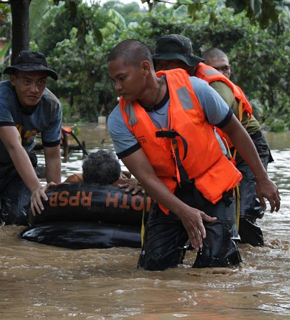 Philippine National Police rescuers use a rubber boat to evacuate a resident after flash floods brought by Typhoon Washi