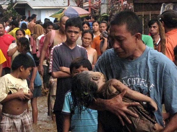 A father cries as he carries the body of his child, who was among hundreds killed by Typhoon Washi