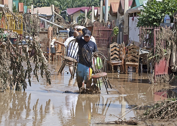 A resident carries items he salvaged from his damaged shanty after the flash floods hit Iligan city, southern Philippines