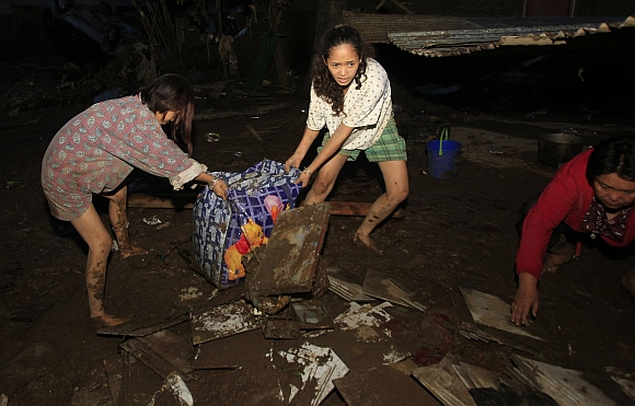 Residents retrieve belongings in Balulang village after the village was hit by flashfloods